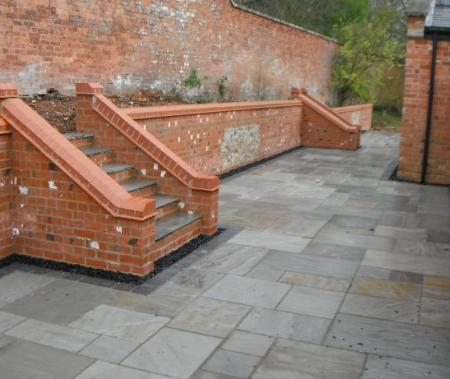 newly paved patio with steps providing easy access to raised beds