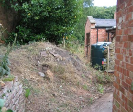 Collapsed retaining wall mud needs to be removed and wall rebuilt